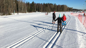 Äiti hiihtää kahden lapsen kanssa Helsingin Paloheinässä. On talvi ja aurinko paistaa.