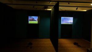 Flera bås med svarta väggar, i båsarna finns tv-skärmar med en animerad virtuell verklighet.