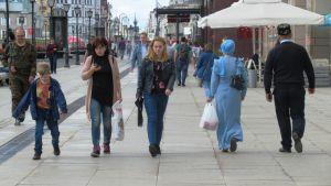 Tatarer och ryssar vandrar sida vid sida på gatan i Kazan.