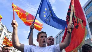 Två män viftar med Nordmakedoniens, Albaniens och EU:s flagga.