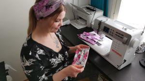 Yrittäjä Leeni-Elina Haimi pitää käsissään kukkakuosista maskia.