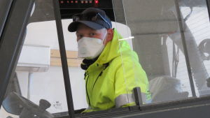 EN man inne i i hytten i en gaffeltruck. Han har neongula arbetskläder och keps, men det mest speciella är att han har munskydd. Det beror på coronaepidemin och regler på mannens arbetsplats.