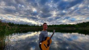 Kvinna står vid vatten,kvälls himlen speglar sig i vattnet. Hon bär en gitarr