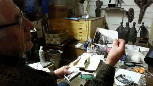 Ossi Somman selailee arkistojaan ateljeessaan
