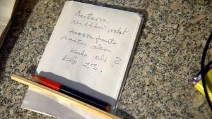 Kaksi kynää ja valkoinen paperi, jossa on käsinkirjoitettua tekstiä.