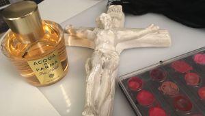 Ett vitt krusifix och en parfymflaska och läppfärgspalett på ett bord.
