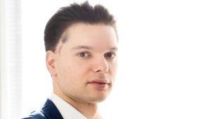 Kasimir Baltzar katsoo kameraan päällään sininen puku.