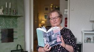 Lena Marander-Eklund sitter framför en kakelugn och läser ur boken Hemma och fru