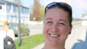 En kvinna med solglasögon på huvudet ler.