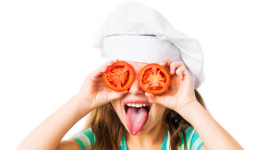 En flicka håller två skivor tomater framför sina ögon och sticker ut sin tunga.