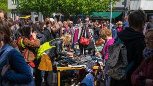 Loppmarknad utomhus med en massa folk.