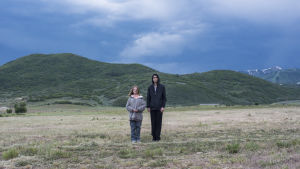 Charlie och Peter står bredvid varandra på ett öppet stor fält med höga berg i bakgrunden.