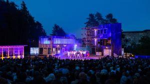 En utomhusscen med en kuliss som föreställer bostadshus och en butik upplysta i kvällsmörker. Många skådespelare och dansare på scen och stor publik vid scenen.