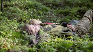 Adela Pajunen ja Marko Leppänen makaavat retkipatjoilla metsän keskellä ja tuijottelevat taivaalle.