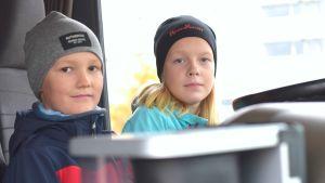 Två barn, en flicka och en pojke, sitter i förarhytten på en lastbil.