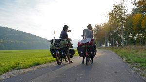 Två cyklister har stannat på en väg och blickar framåt. Vi ser dem bakifrån. Den ena pekar på något. Till vänster syns ett berg. Cyklarna är fullastade med väskor.
