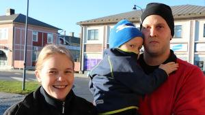 En ung leende kvinna står bredvid en ung man som håller ett barn i famnen.