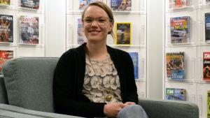 Sandra Jernström sitter i en grön fotölj, tidningar i bakgrunden.