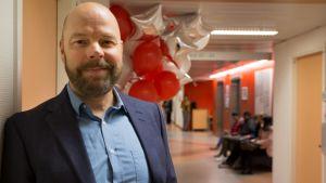 Suomen Diakoniaopiston rehtori ja toimitusjohtaja Juha-Petri Niiranen nojaa koulun käytävän seinään.