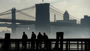 Dimma över Brooklyn Bridge med några män i förgrunden