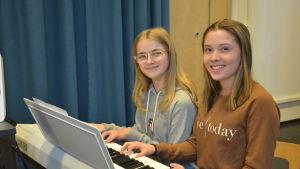 Två flickor sitter och spelar vid en keyboard.