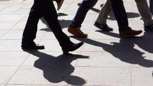 Ihmisiä jalkakäytävällä.