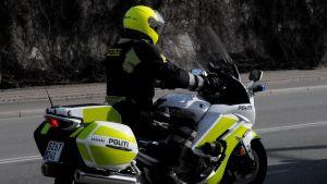 En dansk polis på polisens motorcykel. Det står polis på danska på motorcykeln.