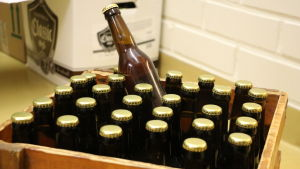 En träkorg fylld med ölflaskor.