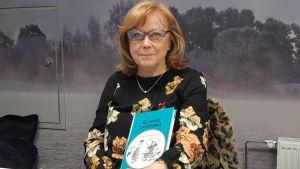 äldre dam i rött hår, svart blus och glasögon sitter med bok i famnen