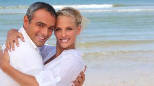 en äldre man kramar om en yngre kvinna på stranden