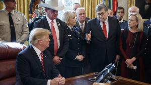 President Trump sittande vid skrivbord, med folk omkring sig, bla jusititieminister Barr och man med stor cowboyhatt.