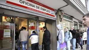 En grupp män köar in till arbetskraftsbyrån i Madrid, Spanien.