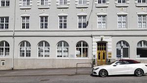 En vit byggnad framför en asfaltväg. En bil står parkerad framför byggnaden.