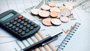 En miniräknare, penna, papper med statistik och mynt på ett bord.