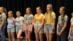 Flickor står på rad och sjunger