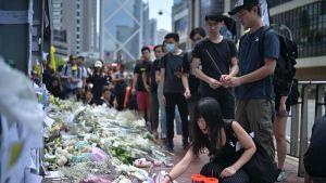 Demonstranter lägger ner blommor på en minnesplats för den unga demonstranten som dog i en olycka på lördagen.