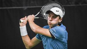 Emil Ruusuvuori håller en tennisklubba över sin axel.