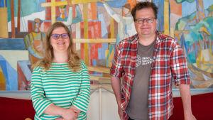 Museichef Laura Lotta Andersson och Arkeolog Jan Fast står framför en färggrann tavla på Hangö museums kansli.
