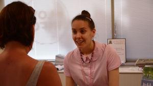 Kvinna betjänar en annan kvinna i kassan i en turistbyrå.