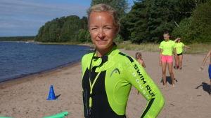 Charlotta Andström på en sandstrand med barn och ungdomar i bakgrunden.