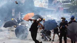 Demonstrant i Hongkong svarar på polisens tårgas med att kasta en tegelsten.