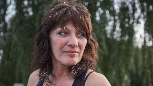 Tummatukkainen nainen lähikuvassa, hiuksissa sahanpurua