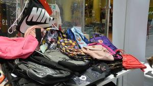På ett bord ligger kring trettio ryggsäckar i olika färger och modell.