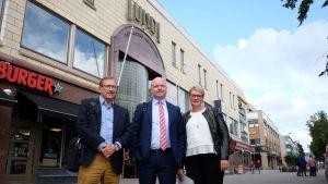 Två män och en kvinna står framför köpcentret Lundi.