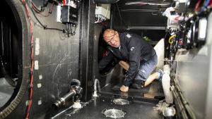 Suomalainen yksinpurjehtija Ari Huusela demonstroi juuri remontoidun Ariel II -aluksensa liikkumisen vaikeutta. Polvisuojat ja kovassa merenkäynnissä myös kypärä tulevat tarpeeseen.