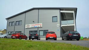 Företagsbyggnad med bilar utanför.