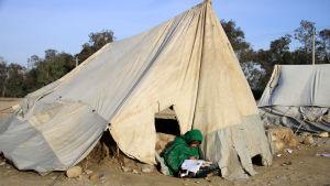 En flicka sitter och läser utanför ett tält. Tältet är gjort av presenning som har spänts mot marken. Det är smutsigt och har hål.