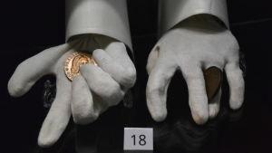 Vita handskar med guldmynt i dem.