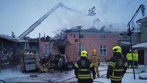 Brandmän fotade bakifrån står och tittar på ett trähus som är brandskadat och som det ryker från.