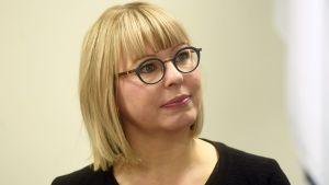 En kvinna med blond page och svartbågade glasögon.